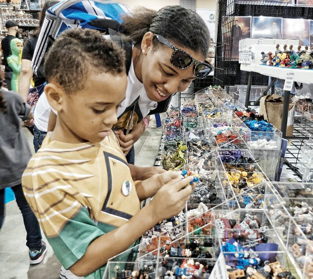 Brandon Jones and his sister, shanea Mercer, of Newport News gaze at action figures saturday at Wizard World Comic Con Richmond. the multi-genre entertainment and comic convention attracted elaborately costumed fans and others to the three-day event at the Greater Richmond Convention Center in Downtown. several celebrities also participated.