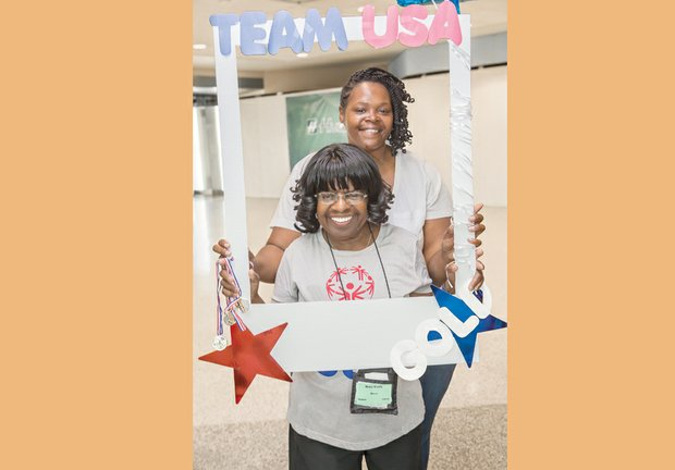 Mary Davis, front, enjoys an Olympic hero's welcome Monday night when she arrives home at Richmond International Airport. Among the bevy of family and friends greeting her was counselor Keisha Walker. Left, friends hold a sign to show their pride in Team Virginia's medal-winning efforts.