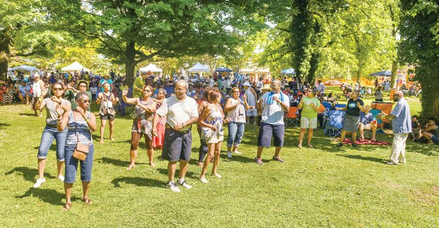 Music, food and fun - Festivalgoers perform a line dance Saturday at the 7th Annual Jazz & Food Festival at St. Elizabeth Catholic Church in Highland Park.