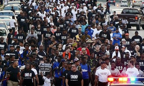 The weather was a steamy 82 degrees on August 16 around 5 p.m. when men in black t-shirts began gathering ...