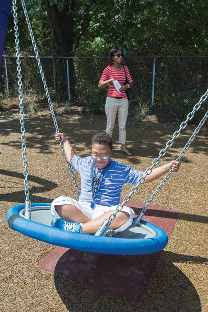 Fun at ARCpark- Joshua Parson, 11, enjoys a swing with his mother, Natalia Parson, nearby. The 2.4-acre park is open daily from dawn to dusk. It is the first recreation area designed to accommodate persons with disabilities in Central Virginia, according to Greater Richmond ARC, and includes a wheelchair-accessible tree house and fitness equipment. The park borders the organization's headquarters at 3600 Saunders Ave.