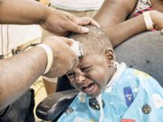 Desean Holland gets a back-to-school haircut from barber Donnell Bates.