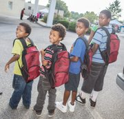 From left, Jandre, Nasir, Seneca and Jason Hackett are ready for the start of school with new book bags filled with school supplies.