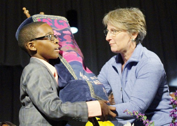 """Elijah Coles- Brown, 11, receives the Torah — a Hebrew scroll of the five biblical books of Moses — from Rabbi Amy Schwartzman of Falls Church during the VUU stop on the NAACP's """"Journey for Justice."""" The Torah accompanied marchers on the journey."""