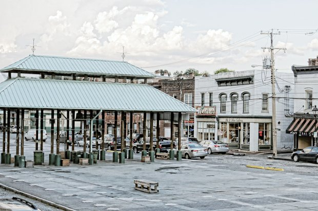 This is the new look of Richmond's Farmers' Market on 17th Street in Shockoe Bottom. Most of the green-topped sheds, fixtures since 1986, are gone, creating a more open space for public events. The remaining sheds allow the 236-year-old market to remain in operation. The shed removal, which cost about $88,000, is the first step in a planned $2.5 million facelift for the market, including the installation of promenades and new landscaping. This photo was taken a few days before the start of the UCI Road World Championships.