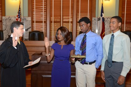 Jacquie Baly is sworn into office by Justice Brett Busby her sons Raphael and Alex Chaumette by her side