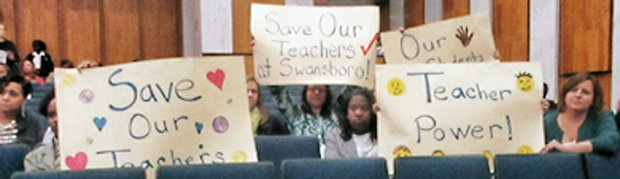 Teachers at Monday's Richmond School Board meeting hold signs showing their opposition to the school administration's plan to move some elementary school teachers from their current classrooms to other schools.