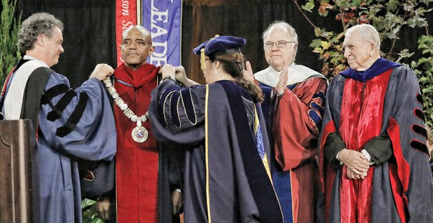 Historic inauguration at UR - Dr. Ronald A. Crutcher, center, receives the sterling silver Presidential Chain of Office at the University of Richmond from President Emeritus Edward L. Ayers and Dr. Kristine A. Nolin, university marshal and associate professor of chemistry.