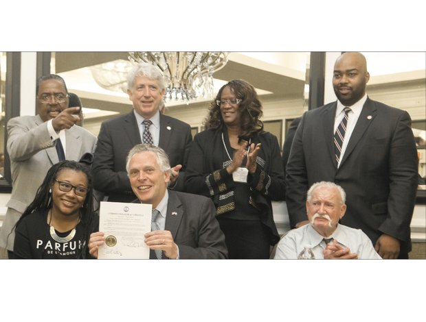 Gov. Terry McAuliffe, seated center, restores the voting rights of two felons who are rebuilding their lives, Chanté Hamlin, seated left, and Bobby Jack Blevins, seated right, during the state NAACP convention last weekend. Looking on, from left, are interim state NAACP Executive Director Jack Gravely, state Attorney General Mark Herring, outgoing state NAACP President Carmen Taylor and Henrico Delegate Lamont Bagby.