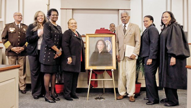 Judge Jamison retiring // Family and friends join in unveiling the portrait of outgoing Judge Birdie Hairston Jamison, right, that will hang in the Richmond General District Court. With her at Friday's ceremony at the Manchester Courthouse are, from left: Sheriff C.T. Woody Jr., Judge Jamison's sister, Paige Hairston, Delegate Delores L. McQuinn, former Delegate Jean W. Cunningham, Richmond General District Court Chief Judge D. Eugene Cheek, former state Sen. Henry L. Marsh III and Judge Jamison's other sister, Mable Lewis. Judge Jamison, 57, is the dean of the state's traffic court judges. She began hearing cases in Richmond in 1991. Her tenure on the court officially ends Tuesday, Nov. 30. She must step down because the General Assembly declined to reappoint her to a new term last January. Numerous speakers at the retirement ceremony lauded her service to the court.