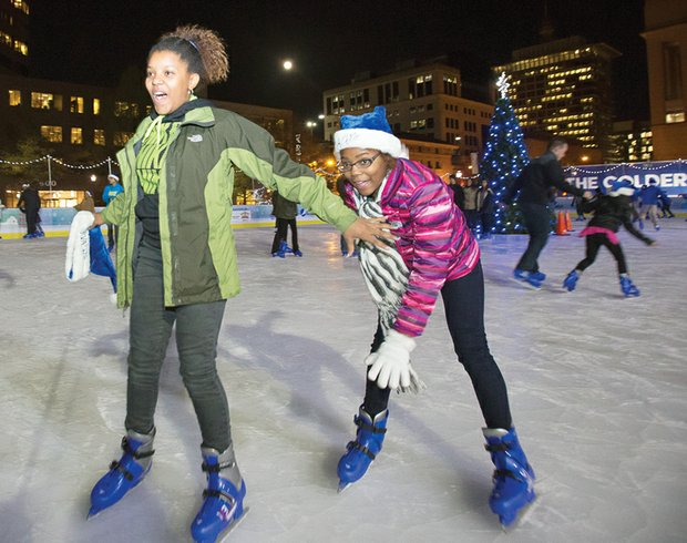 Brimming with excitement, Jessica Henderson, 14, reaches back to help Jordyn Henderson, 12, stay on her feet as the two skate at the city's outdoor rink in the 600 block of East Broad Street in Downtown. They joined dozens of other skaters at last Friday's opening ceremony for RVA On Ice, which debuted its sixth season with music, games, activities and prizes. American Idol finalist Rayvon Owen of Henrico County and the Richmond Boys Choir performed at the kickoff event that was hosted by Richmond Mayor Dwight C. Jones. The rink will be open for skating through Sunday, Jan. 3.