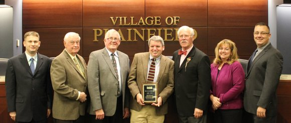 Plainfield village planner Michael Garrigan was honored by the village for his 15 years of service before he takes on ...