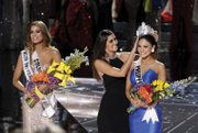 """Miss Colombia Ariadna Gutierrez Arevalo, left, stands by as the Miss Universe crown is transferred Sunday to the actual winner of the pageant, Miss Philippines Pia Alonzo Wurtzbach. Host Steve Harvey mistakenly announced the runner up as the winner. He apologized, asking the loudly booing audience not to """"hold it against the ladies."""" Miss Universe 2014 Paulina Vega placed the crown on the head of the winner."""