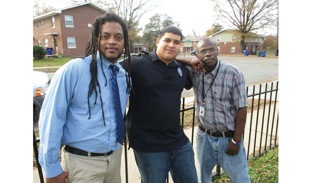 Richmond Police Officer Reynaldo Perez is flanked by Shaun Moore, left, and Jeffrey Perry, who found jobs after participating in Bridging The Gap One Human At A Time, a program the officer started. Location: Mosby Court public housing community.
