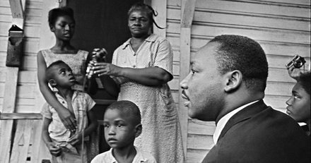 Dr. Martin Luther King Jr., right, chats with Greenwood African Americans on their front porch during his door-to-door campaign, telling all African Americans to register to vote in Greenwood, July 21, 1964.