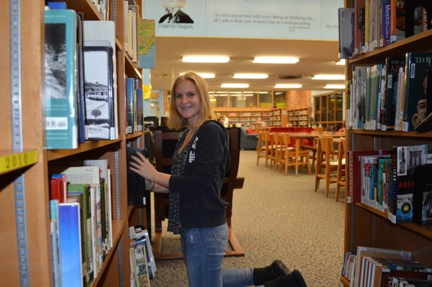 Tess Spesia helps re-shelve books at the Joliet West High School library on Martin Luther King Day.