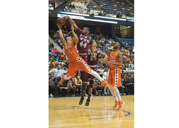 Virginia State University's Javon Moore, No. 5, is fouled by Virginia Union University's Devin Moore who attempts to block the shot during Sunday's Freedom Classic at the Richmond Coliseum. The game was a squeaker, with the VUU Panthers defeating the VSU Trojans 70-68.