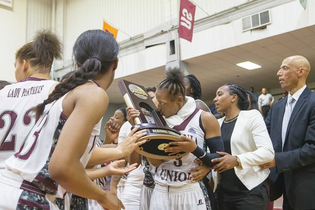 Virginia Union University's Kiana Johnson kisses the NCAA regional championship trophy she and her teammates were awarded after Monday night's victory over West Liberty University at Barco-Stevens Hall.