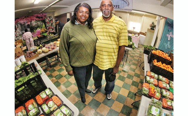 Betty and John Thombs display the fresh vegetables and fruits they collected from area stores on Tuesday. The food is given away in the social hall at Zion Baptist Church, 20th and Decatur streets, on South Side. The hunger-fighting couple has been quietly creating this pop-up food-giveaway stand daily for more than five years.