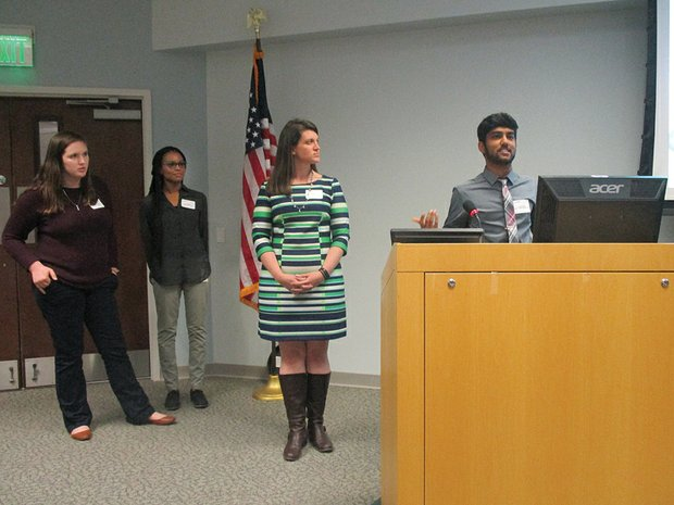 Left to right, College of William & Mary students Jessica Lee and Caris Wright and team adviser Dr. Elizabeth Yost listen as Akshay Murthy pitches the Simply Connected Android-user interface.