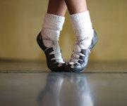 Morgan Bullock poses in front of a mirror during a recent practice. She shows off the special shoes she uses to perform the fast-paced Irish dance routines.
