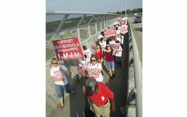 Marchers cross the Martin Luther King Jr. Memorial Bridge on Monday en route to a rally outside Richmond City Hall seeking more money for Richmond Public Schools.