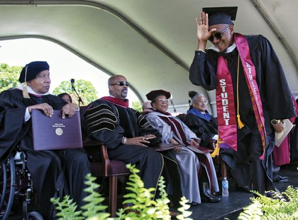 """Football star Kevius Morgan happily reacts after receiving his diploma. Looking on, from left, are Dr. Walton Belle, who was awarded an honorary doctorate for his 45 years of service as physician to VUU's athletic teams; Dr. Frederick D. Hayes III, an activist minister who also received an honorary doctorate; Carolyn W. Jacobs, president  of the VUU National Alumni Association; and commencement speaker Congressman Robert C. """"Bobby"""" Scott."""