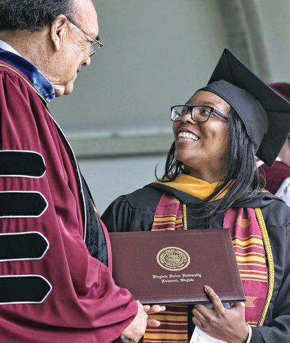 VUU President Claude G. Perkins congratulates valedictorian Veronica Pegram of Mechanicsville, who earned her degree in biology.