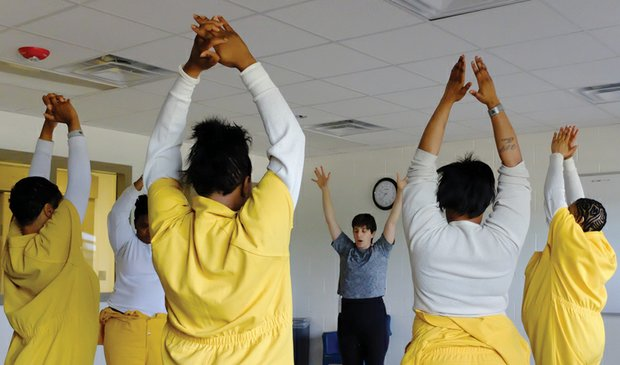 Women participate in a yoga class at the Richmond Justice Center taught by Ellie Burke.