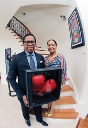 Dr. Monroe Harris and his wife, Dr. Jill Bussey, show boxing gloves autographed by the champ, who grew up in the same neighborhood with them in Louisville, Ky.