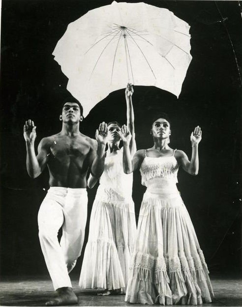 "An iconic photo from a 1960s performance of Alvin Ailey's masterpiece ""Revelation"" captures a man and woman walking forward side-by-side."