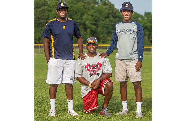 Christopher W. Armstrong, center, who played baseball on the Metropolitan Junior Baseball League's first Inner City Classic team in 1991, is coaching the team of his son, Josiah, right, that will be playing at this year's classic in Chicago. His son, Jujuan, also will play at the classic on the team for younger players.
