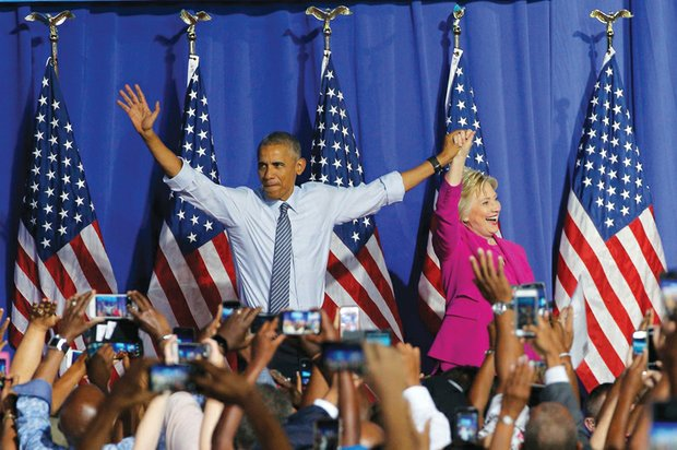President Barack Obama waves with Hillary Clinton, the presumptive Democratic presidential nominee, at a campaign event Tuesday in Charlotte, N.C. Neither the president or Mrs. Clinton were told ahead of time about the FBI announcement or conclusion.