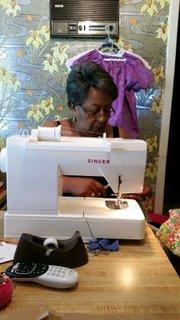 Member of Zeta Gamma Omega Chapter of Alpha Kappa Alpha Sorority, Inc. sewing little dresses for Africa