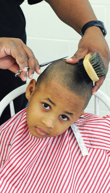 Dapper for School // Jayden Morgan wants to look his best when he starts kindergarten at J.E.B. Stuart Elementary School in Richmond. He got his hair cut last Saturday by Jamaal Umar Abdur-Rahman during the 8th Annual Back-to- School Rally at Martin Luther King Jr. Middle School in the East End. Students also received backpacks and school supplies at the event hosted by Richmond School Board member Shonda Harris-Muhammed. Games, music, food and other activities pumped up the back-to-school spirit.