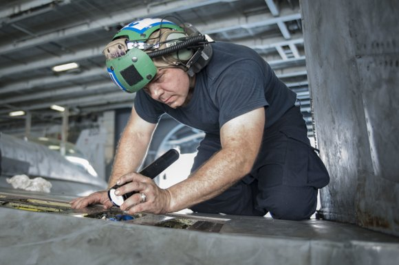 ARABIAN GULF (Aug. 30, 2016) Aviation Structural Mechanic Ronny Smith, from Houston, inspects the panels of an F/A-18C Super Hornet ...