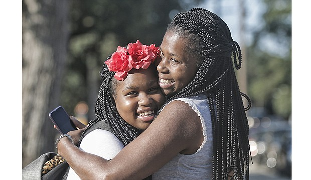 Sixth-grader Ayanna Street, left, and her mother, Yakysha Langhorne, embrace during a first-day-of-school pep talk while waiting at the bus stop Tuesday at Westover Hills Elementary School. The South Side elementary school is Ayanna's hub to get to Binford Middle School in the West End under the new transportation plan.