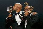 """Funnymen Keegan-Michael Key, left, and Jordan Peele kiss their Emmy Awards after the show. They won the Emmy for outstanding variety sketch series for their comedy show, """"Key & Peele."""""""