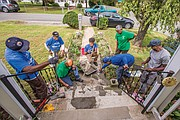 Below, volunteers, from left, Randy Thomas, James Nelson, Harold Hockaday, Derrick Isler, Richard Burwell, Judith Wansley and Charlie Booker work to repair the steps and walkway outside the Highland Springs home of an elderly person.
