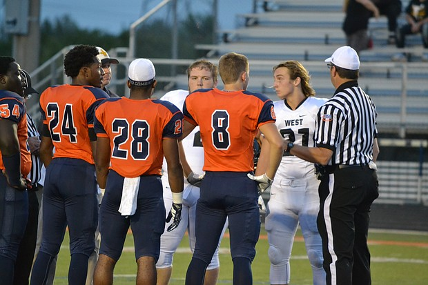 Romeoville Spartans captains greet Joliet West captains before the teams' September 16 matchup at Romeoville.