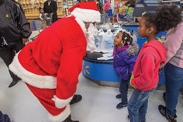 Kevasia Taylor, 5, center, takes a break from shopping to rattle off her detailed Christmas list to Santa Claus, while 10-year-old Quanasia Hubbard waits to share her list during the Prince Hall Masons' Operation Santa Claus last Saturday. Location: Walmart on Sheila Lane in South Side.
