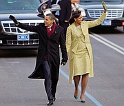Mrs. Obama wears a two-piece lemongrass-hued ensemble by Cuban-American designer Isabel Toledo as she walks down Pennsylvania Avenue with newly sworn-in President Obama in January 2009.