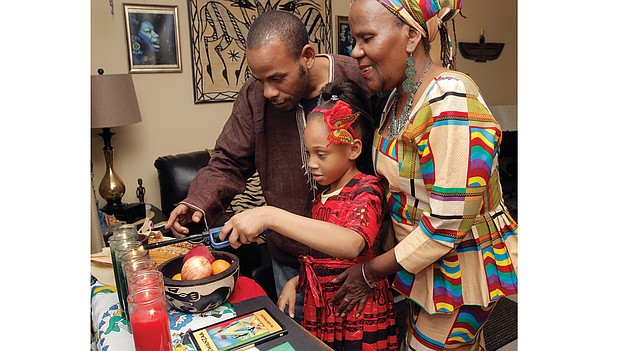Sakara Bey, 8, lights the Kwanzaa kinara with her father, Hakim Bey, and grandmother, Shakila Davis, on Wednesday at Mrs. Davis' Henrico County home. The family is celebrating the third day of Kwanzaa, ujima, or collective work and responsibility.