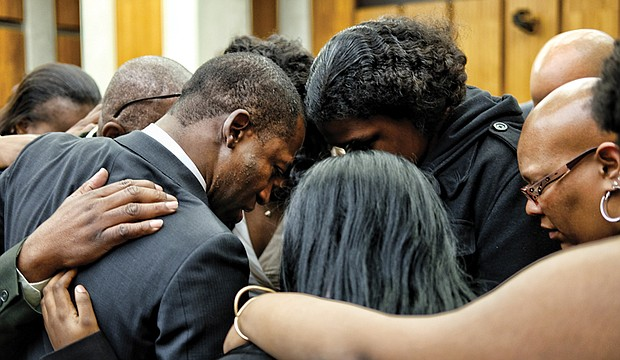 Family members embrace in a prayer circle with Levar