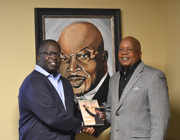 """Author Calvin Quarles gives Rev. Dr. David G. Latimore a copy of his new book """"The Panther at the Cross"""" at Mount Zion Baptist Church in Joliet in front of a painting of the former elected pastor Rev. Dr. Issac Singleton."""