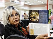 Evelyn Hawkins, a retired John Marshall High School librarian, shows the current edition of National Geographic magazine and the skull now being analyzed at the Smithsonian. Mrs. Hawkins' family now owns the  Southampton County farm where Nat Turner was captured after the enslaved people's uprising in 1831.