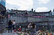 Visitors pay their respects to the victims of a racially-motivated stabbing attack on a MAX light rail train at the Hollywood/42nd Avenue Transit Center. The front of the station's concrete façade has become a makeshift memorial.