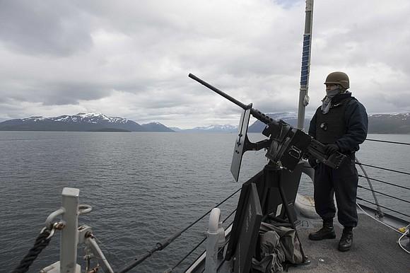 Fire Controlman 2nd Class Luis Moreno, from Houston, mans a .50-caliber machine gun aboard the Arleigh Burke-class guided-missile destroyer USS ...