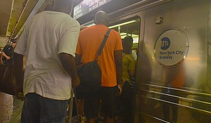 Passengers board the subway at the 125th Street Station