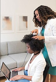 Chambers-Harris performing a  hair and scalp consultation as a Certified Hair Practitioner of Trichology (International Association of Trichology Certified)